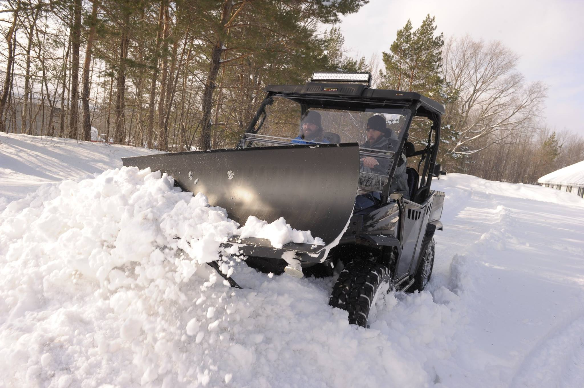 a side by side utv with a snowplow attachment