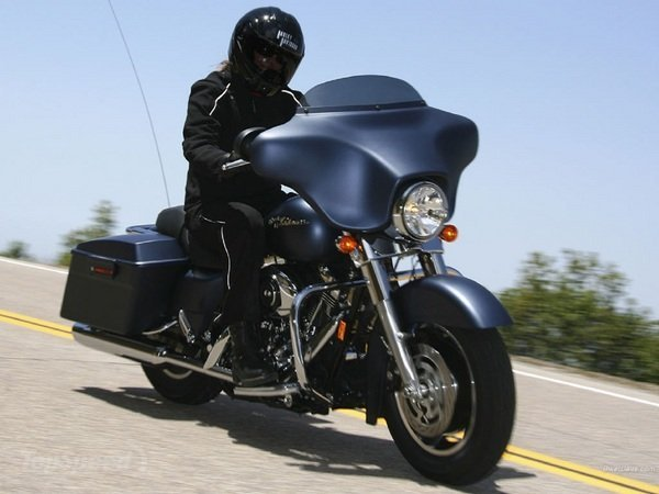Man in all black riding an all black motorcycle