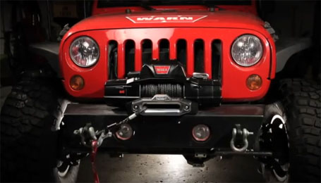 Red Jeep wrangler with a Warn winch